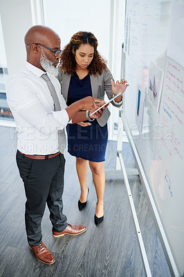 Buy stock photo High angle shot of two business colleagues using a tablet while working together in their office