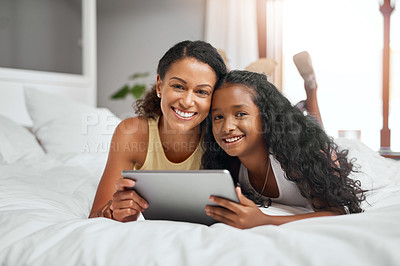 Buy stock photo Shot of a mom and daughter lying on bed with a digital tablet