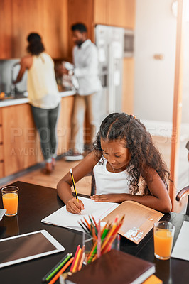 Buy stock photo Shot of a little girl doing her homework with her parent in the background