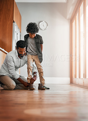 Buy stock photo Shot of a man tying his little boy's shoelaces
