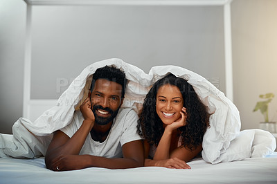 Buy stock photo Cropped shot of a young attractive couple in bed at home