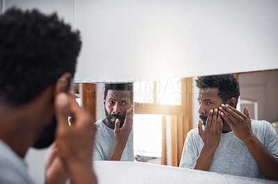 Buy stock photo Cropped shot of a handsome young man examining his face in a mirror in the bathroom at home