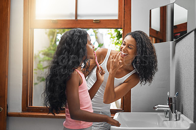 Buy stock photo Cropped shot of an attractive young woman and her daughter brushing their teeth in the bathroom at home