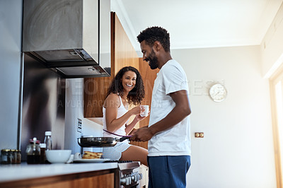 Buy stock photo Cropped shot of a handsome young man cooking in the kitchen while his wife watches on