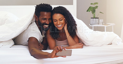 Buy stock photo Cropped shot of a young attractive couple taking a selfie in bed at home