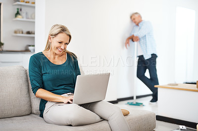 Buy stock photo Shot of a mature woman using a laptop at home while her husband sweeps in the background