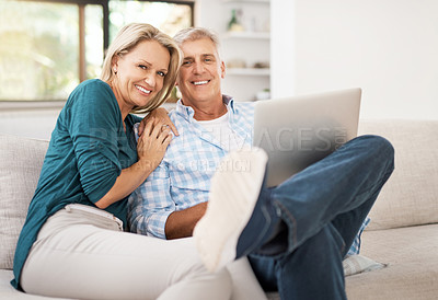 Buy stock photo Portrait of an affectionate mature couple using a laptop while sitting on the sofa together at home