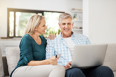 Buy stock photo Shot of an affectionate mature couple using a laptop while sitting on the sofa together at home