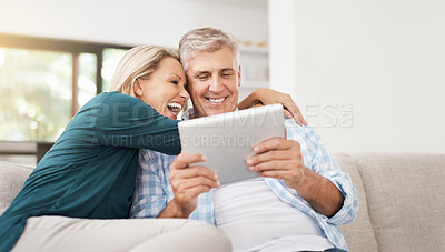 Buy stock photo Cropped shot of an affectionate mature couple using a tablet while sitting on their sofa at home