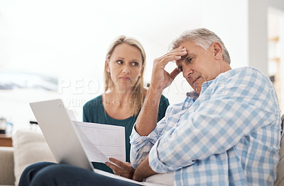 Buy stock photo Cropped shot of a mature couple looking stressed out while doing their budget at home
