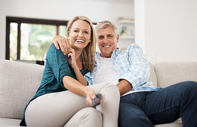 Buy stock photo Cropped portrait of an affectionate mature couple watching television together at home