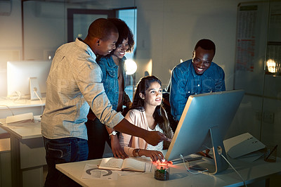 Buy stock photo Shot of a group of colleagues working late together on a computer in an office