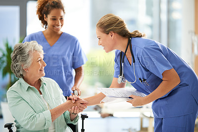 Buy stock photo Shot of an attractive female nurse holding medical records while shaking hands with her wheelchair-bound senior patient in the hospital
