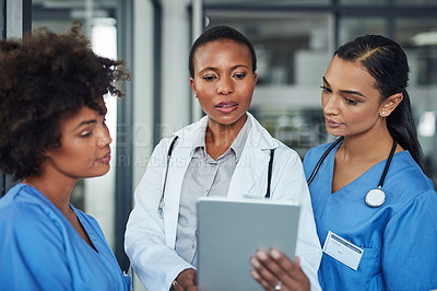 Buy stock photo Shot of a group of medical practitioners working together on a digital tablet in a hospital