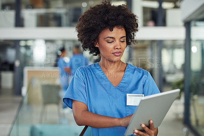 Buy stock photo Shot of a nurse using a digital tablet in a hospital