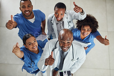 Buy stock photo Portrait of a group of medical practitioners showing thumbs up together in a hospital