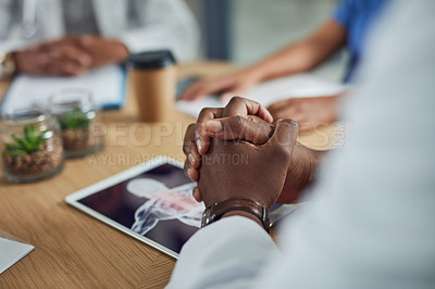 Buy stock photo Closeup shot of an unrecognizable doctor using a digital tablet during a meeting with his colleagues in a hospital