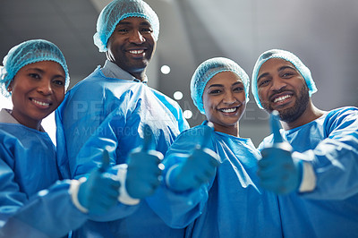 Buy stock photo Portrait of a group of surgeons showing thumbs up in a hospital