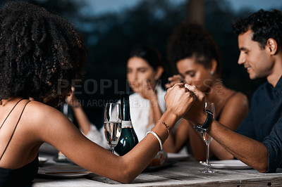 Buy stock photo Cropped shot of a group of friends saying grace before they eat