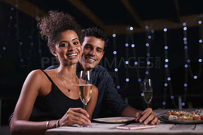 Buy stock photo Cropped shot of an affectionate young couple having a romantic dinner in a restaurant