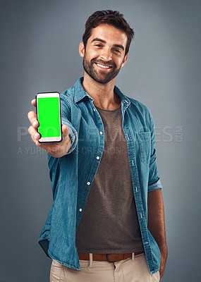 Buy stock photo Studio shot of a handsome young man showing a mobile phone with a green screen against a grey background