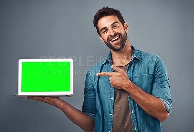 Buy stock photo Studio shot of a handsome young man showing a laptop with a green screen against a grey background
