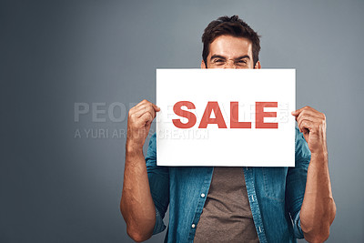"Buy stock photo Studio shot of a handsome young man holding a placard with the word ""sale"" on it against a grey background"