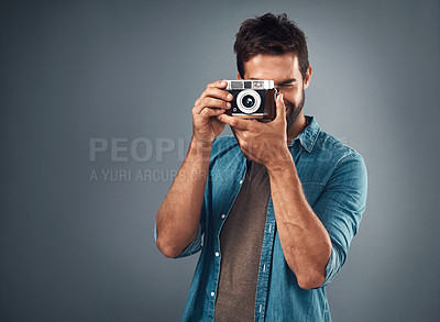 Buy stock photo Studio shot of a handsome young man using a camera against a grey background