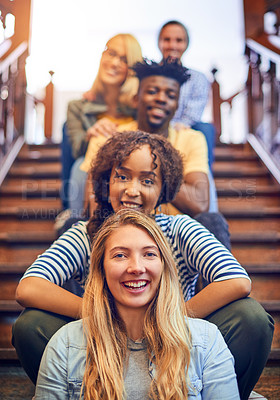 Buy stock photo Portrait of a group of diverse university students sitting in a row on the staircase on campus