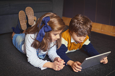Buy stock photo Shot of a little boy and girl using a digital tablet at home