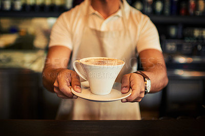 Buy stock photo Closeup of an unrecognizable man holding a freshly brewed cup of coffee while standing inside of a restaurant during the day