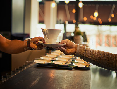 Buy stock photo Shot of an unrecognizable barman handing over a cup of coffee over the counter to a customer inside of a restaurant during the day