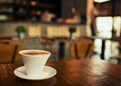 Buy stock photo Shot of a freshly brewed cup of coffee standing on a table by it's own inside of a restaurant during the day