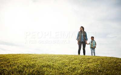 Buy stock photo Shot of a woman holding her little girl's hand as they walk outdoors