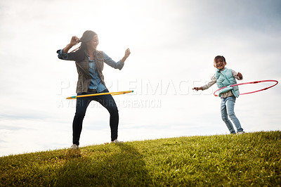 Buy stock photo Shot of a little girl and her mom having a hula hoop challenge