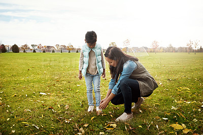 Buy stock photo Shot of a mother tying her little girl's shoelaces
