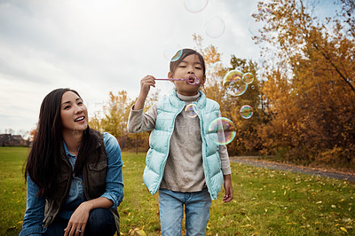 Buy stock photo Shot of a mother and her little daughter playing with bubbles outdoors