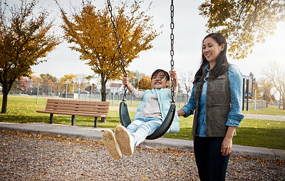 Buy stock photo Shot of a mother pushing her little daughter on a swing at the park