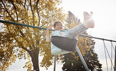 Buy stock photo Portrait of an adorable little girl playing on a swing at the park