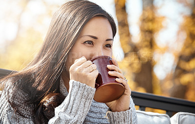 Buy stock photo Shot of an attractive young woman having a relaxing coffee break on an autumn day in a garden