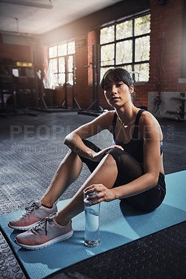 Buy stock photo Shot of an attractive young woman sitting on a exercise mat at the gym