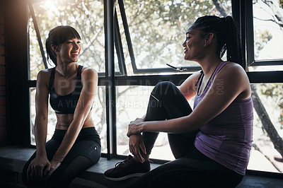 Buy stock photo Shot of two friends chatting while out for a workout at the gym