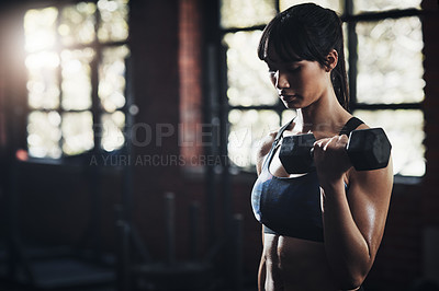 Buy stock photo Cropped shot of a beautiful young woman lifting dumbbells at the gym