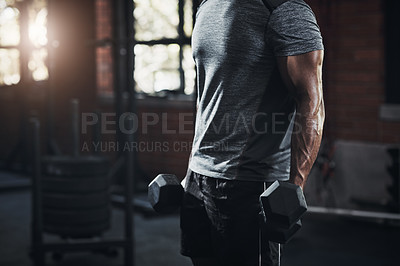 Buy stock photo Cropped shot of an unrecognizable man working out with dumbbells