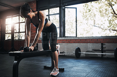 Buy stock photo Shot of a beautiful young woman lifting dumbbells at the gym