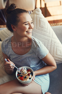 Buy stock photo Shot of an attractive young woman eating her breakfast while relaxing on the sofa at home