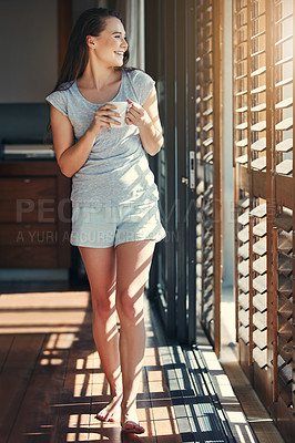 Buy stock photo Shot of an attractive young woman enjoying her morning coffee while standing in the kitchen at home