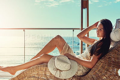 Buy stock photo Shot of an attractive young woman relaxing outside on her balcony in the sun