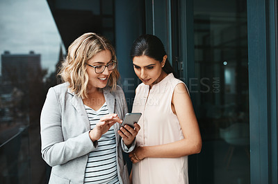 Buy stock photo Shot of two businesswomen using a cellphone together on the office balcony