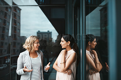 Buy stock photo Shot of two businesswomen having a discussion on the office balcony